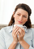 Serene woman holding a cup of coffee Stock Photos