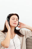 Serene woman listening to the music on the sofa. At home Stock Image