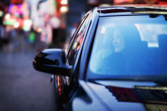 Serene woman looking through car window at the city nightlife Royalty Free Stock Photography