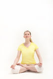 Serene woman in lotus position meditating. Serene woman sitting on the floor in the lotus position meditating while practising yoga on a white studio background Stock Photography