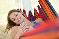 Serene woman lying in hammock with smartphone Stock Images