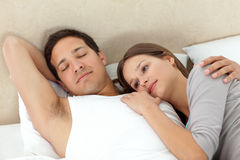 Serene woman lying on her boyfriend's arms. While sleeping in their bedroom Royalty Free Stock Photography