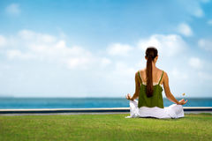 Serene woman meditating front of sea. Back view Stock Photo