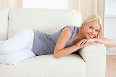 Serene woman resting on a sofa. While looking at the camera Royalty Free Stock Photography