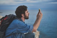 Serene young man taking photo of picturesque ocean. Peaceful male tourist is photographing sea landscape with inspiration. He is squatting with backpack on back Royalty Free Stock Image