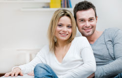 Serene young smiling couple. Young serene couple looking at camera together in their living room at home Royalty Free Stock Photo