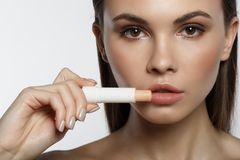 Serene young woman applying hygienic lipstick. Close up of beautiful female face. Calm girl is holding chapstick near her lips. Isolated royalty free stock photos