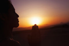 Serene young woman with hands together in prayer pose  in the desert in China, silhouette, sun setting Stock Photography