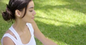 Serene young woman meditating on a green lawn stock video