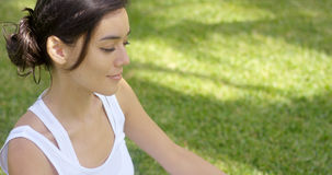 Serene young woman meditating on a green lawn Royalty Free Stock Image