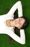 Serene young woman relaxing. Outdoor in fresh grass Royalty Free Stock Photography