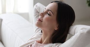 Serene young woman relaxing on sofa breathing air, close up