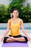 Serene young woman sitting in lotus position outdoors. Serene young woman sitting in lotus position while practicing Hindu yoga outdoors Royalty Free Stock Photo