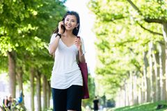 Serene young woman walking in the park. Serene beautiful young woman smiling while walking in the park in summer Stock Image