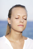 Serenity. Woman at the seaside with closed eyes royalty free stock images