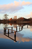 Serenity. A serene scene of a partially submerged fence reflecting on almost still water, against an evening sky and colourful trees Royalty Free Stock Photo