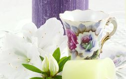 Serenity. Candles, cups and flowers always make a wonderful center piece for any table or a on a tray for tea, this was created by using a cut glass cake plate royalty free stock image