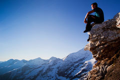 Serenity. Young man sitting on rock above mountain range royalty free stock photos