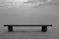 Serenity Bench. Lone bench on a pier overlooking the water Royalty Free Stock Photos