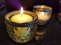 Serenity calming candles. Two lit votive candles in glass holders close-up on marble table Stock Images