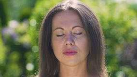 Serenity on face of beautiful woman meditating in park outdoors, close-up dolly stock video
