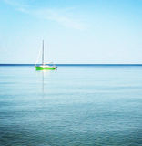 Serenity. Green sailing boat on blue tropical ocean waters Stock Images