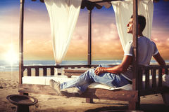 Serenity man relaxing on a canopy bed at the sunset beach. Amazing sunset and man lying enjoying the peace and serenity. Vacation. Four post canopy wooden bed Stock Image