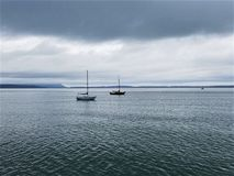 Serenity on Puget Sound. Sailboats sit peacefully in Puget Sound as an approaching storm threatens to disrupt the serenity Royalty Free Stock Photos