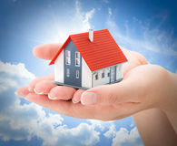 Serenity real estate concept. House in hands Stock Photography