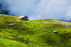 Serenity serene lonely scenery background concept. House in hills in mountins on alpine meadow in clouds Stock Images