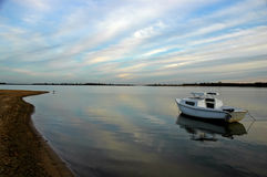 Serenity Shores. A deserted boat is at rest along the shore of a suburban lake Royalty Free Stock Images