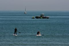 Serfing couple in mediterranean waters of Valencia, Spain Royalty Free Stock Images