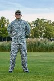 Sergeant in camouflage uniform is stanidng on the grass. Portrait of full-length soldier in the park royalty free stock photos