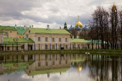 Sergiev Posad, Russia, May 2017. White pond with two swans on the background of ancient architecture on a cloudy spring day. stock images