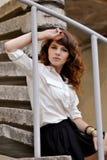 Seria, ribaltamento, la ragazza infelice si siede su grey, scale di pietra e vicino alla ferrovia, parapetto immagini stock