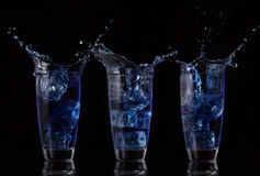 Serial arrangement of blue liquid splashing in glass Royalty Free Stock Photography