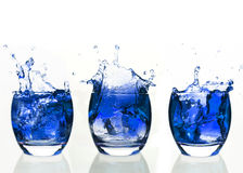 Serial arrangement of blue liquid splashing in tumbler Royalty Free Stock Images
