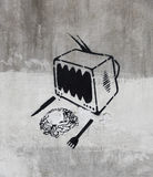 Serial graffiti. Tv eating a human brain, black paint on a grey wall royalty free illustration
