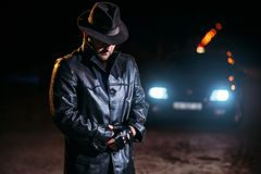 Maniac in black leather coat and hat, back view stock image