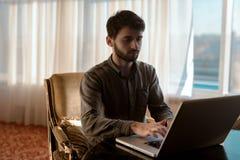 Seriamente e individuo joven del inconformista usar el ordenador portátil, persona trabaja en casa Foto de archivo libre de regalías
