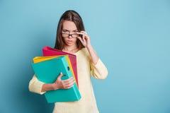 Seriamente olhando a menina esperta com pastas coloridas Imagem de Stock