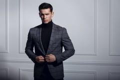 Seriamente retrato de un hombre en el traje negro-gris, presentación elegante cerca de la pared blanca en estudio, en el fondo bl imagen de archivo