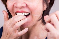 Serie av flossing tänder för asiatisk kvinna med muntlig floss royaltyfri bild