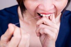 Serie av flossing tänder för asiatisk kvinna med muntlig floss arkivbilder