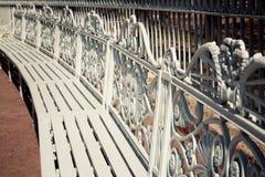 Serie białe ławki z drewnianym siedzeniem i pięknym backrest robić metal z klasyka wzorem Zdjęcie Royalty Free