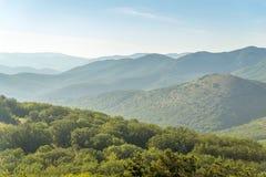 Serie de colinas de la montaña cubiertas con los bosques verdes en alguna parte adentro Foto de archivo libre de regalías