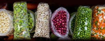 Serie de granos exhibidos en una parada del mercado con las habas, el maíz y las habas foto de archivo libre de regalías