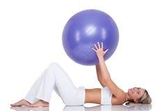 Serie de la aptitud - mujer joven con la bola púrpura Imagenes de archivo
