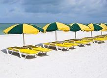 Serie de sillas de salón coloridas en una arena blanca Foto de archivo libre de regalías