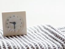 Serie de un reloj análogo blanco simple en la manta, 10/15 Foto de archivo